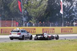 Un auto oficial se detiene al lado del equipo Romain Grosjean Haas F1 Team VF-18 dañado