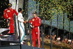 Kimi Raikkonen, Ferrari, 3° classificato, Lewis Hamilton, Mercedes AMG F1, 2° classificato, e Sebastian Vettel, Ferrari, 1° classificato, festeggiano con lo Champagne sul podio