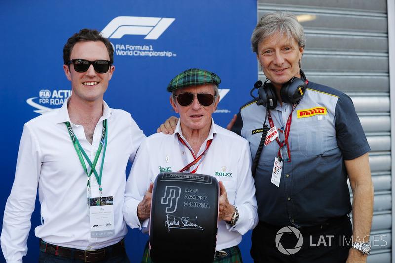 Sir Jackie Stewart tient un pneu avec le message Race Against Dementia