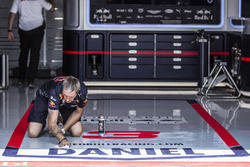 Red Bull Racing mechanic cleans the garage floor