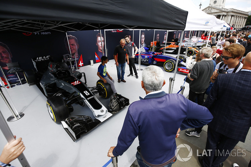 A young fan has his photo taken on the wheel of a Haas F1 Team VF-17