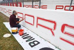 La peinture des publicités Porsche sur le bord du circuit