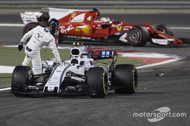 Sebastian Vettel, Ferrari SF70H, passes Lance Stroll, Williams FW40, as he climbs out of his damaged car