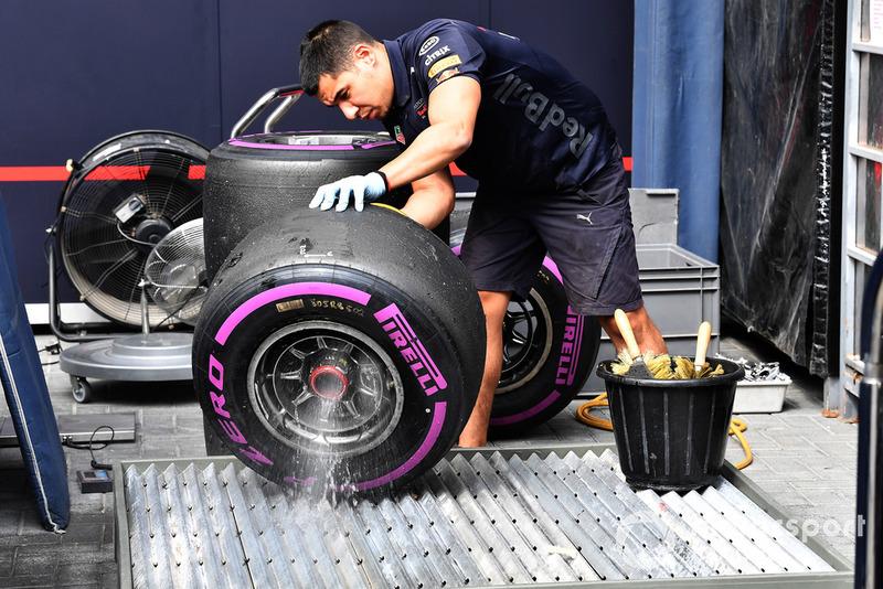 Des mécaniciens Red Bull Racing nettoient des pneus Pirelli