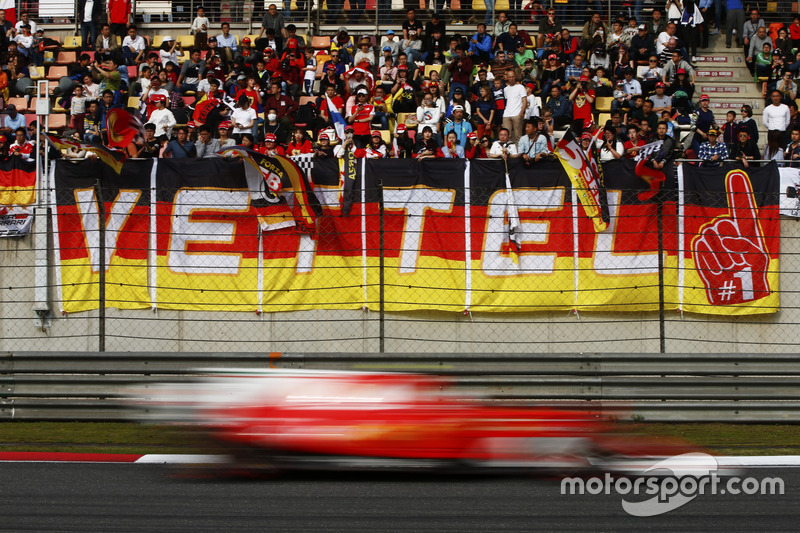 Une Ferrari passe devant une tribune avec de nombreux fans de Sebastian Vettel, Ferrari