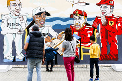 Fans look at artwork depicting Valtteri Bottas, Mercedes AMG F1, Lewis Hamilton, Mercedes AMG F1, Sebastian Vettel, Ferrari, and Kimi Raikkonen, Ferrari, playing backgammon
