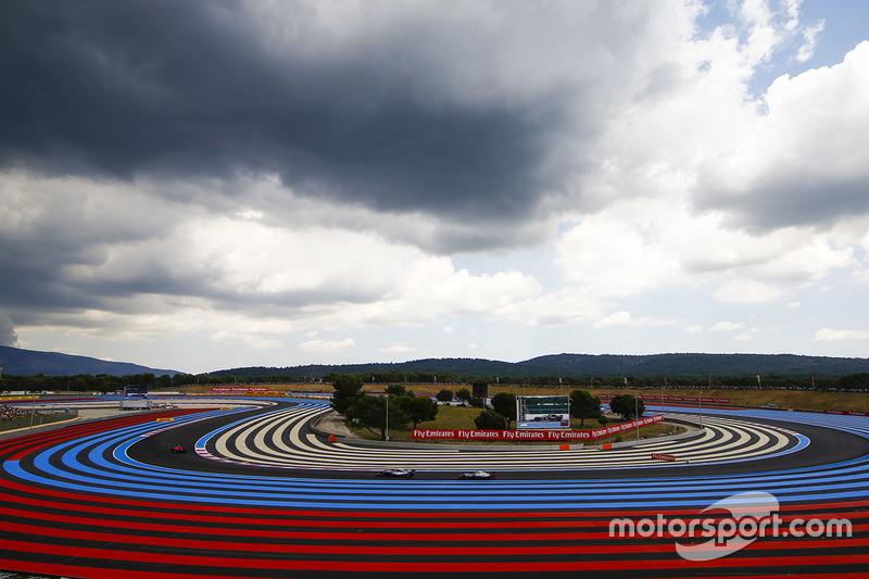 Kimi Raikkonen, Ferrari SF71H, leads Valtteri Bottas, Mercedes AMG F1 W09, and Kevin Magnussen, Haas F1 Team VF-18, under a cloudy sky