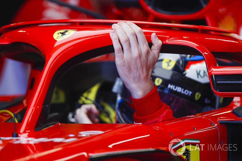 Kimi Raikkonen, Ferrari, rests a hand on his halo