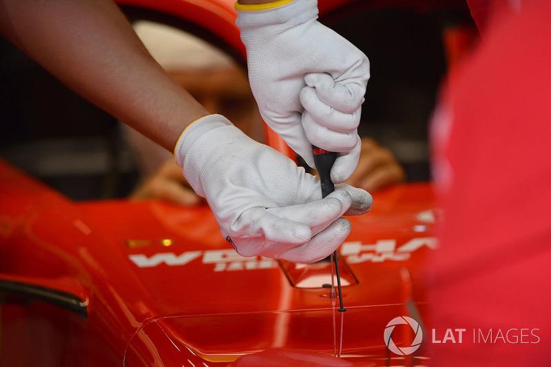 Dettaglio dei guanti sulle mani di un meccanico Ferrari