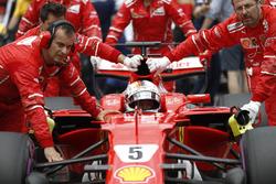 Sebastian Vettel, Ferrari, is pushed onto the grid by mechanics