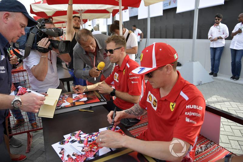Kai Ebel, RTL Presenter talks with Sebastian Vettel, Ferrari and Kimi Raikkonen, Ferrari at the autograph session