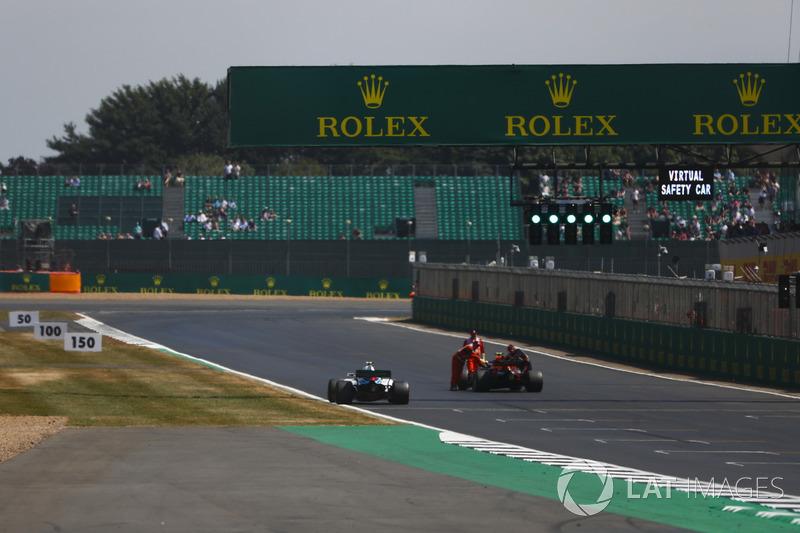 Sergey Sirotkin, Williams FW41, passe devant les commissaires qui évacuent la monoplace de Max Verstappen, Red Bull Racing RB14