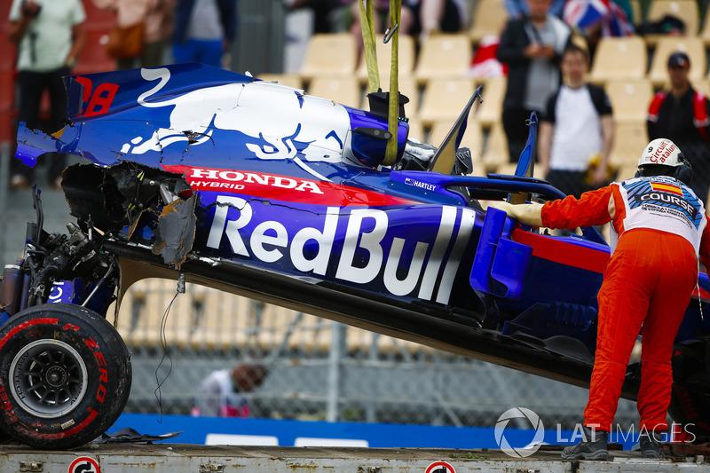 Oficiales retiran el automóvil dañado de Brendon Hartley, Toro Rosso STR13, del circuito cuando la caja de cambios cuelga de la parte posterior