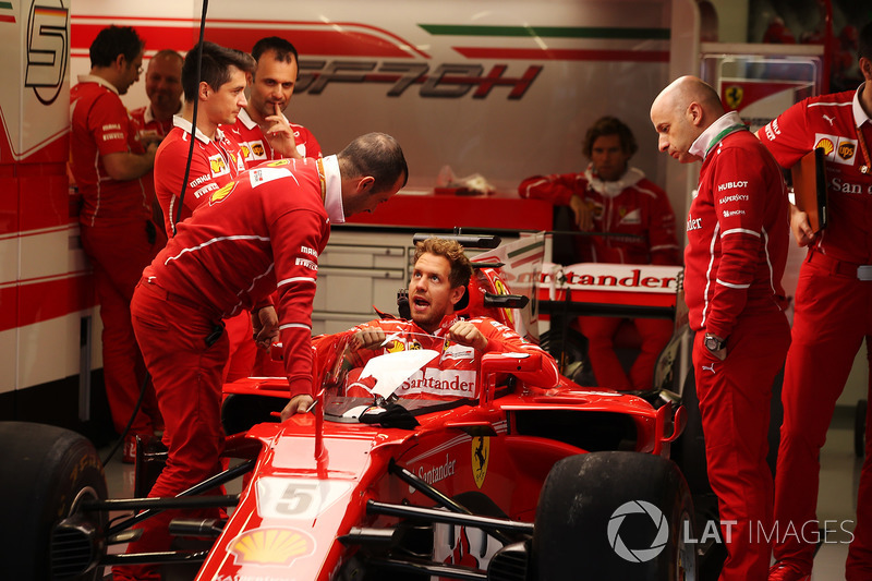 Sebastian Vettel, Ferrari, lowers himself into the cockpit of his car fitted with a new protective s