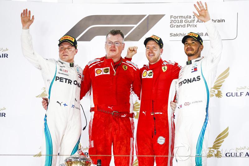 Valtteri Bottas, Mercedes AMG F1, 2nd position, Sebastian Vettel, Ferrari, 1st position, and Lewis Hamilton, Mercedes AMG F1, 3rd position, on the podium with the Ferrari team member who collected the Constructors trophy