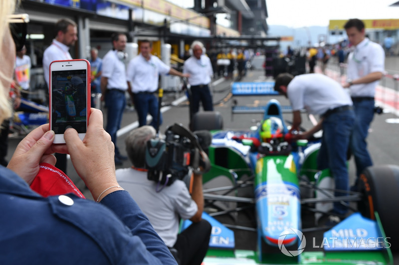 Sabine Kehm, takes a photo of Mick Schumacher, Benetton B194