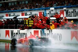 Winner Michael Schumacher, Ferrari F310 takes the flag