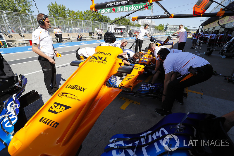 Mechanics work on the Fernando Alonso McLaren MCL33 in the pit lane, and remove the car's nose