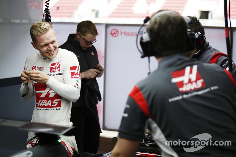 Гонщик Haas F1 Кевин Магнуссен перешучивается с персоналом команды