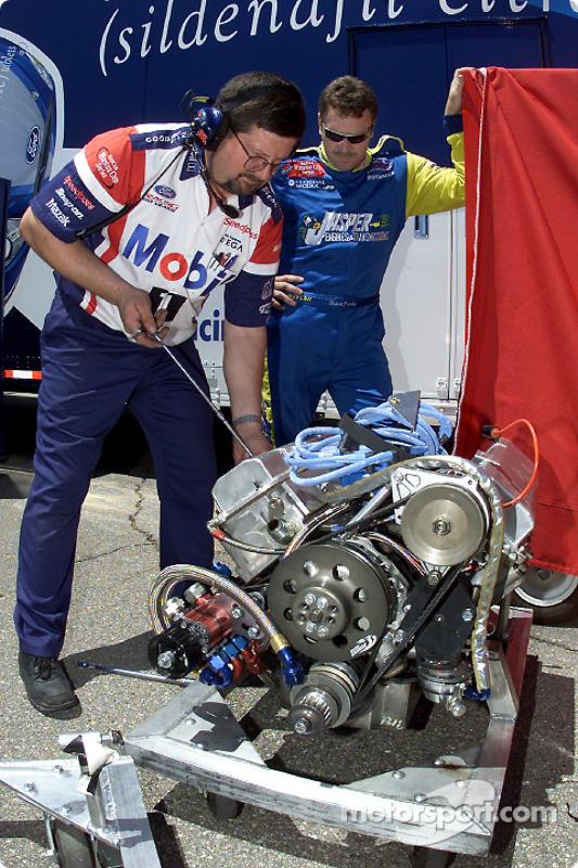 Robert Pressley looks on as a Penske engine technician prepares a motor for the Jasper Ford Taurus
