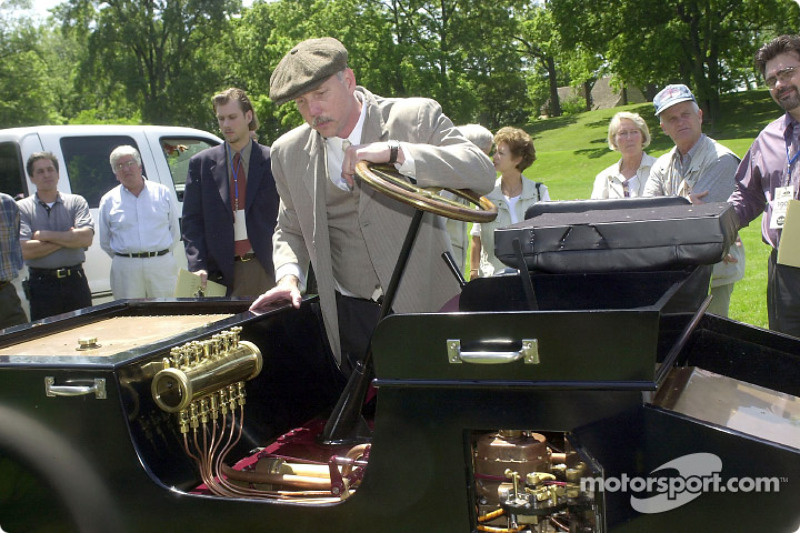 lenn Miller, development engineer at Ford Special Vehicle Engineering, shows off a replica Ford 1901 Sweepstakes vehicle at Greenfield Village in Dearborn, Michigan