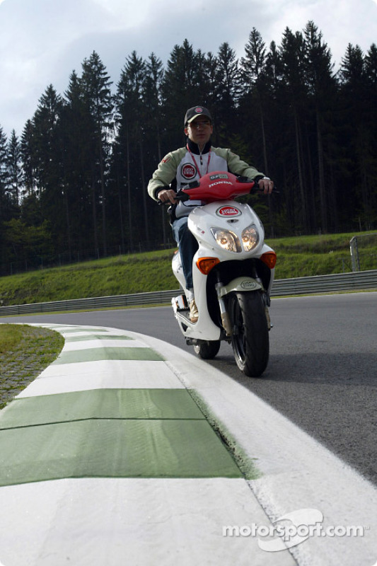Olivier Panis riding his Honda Scooter around the A1-Ring circuit