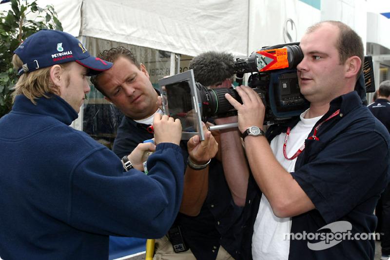 Nick Heidfeld firmando un autógrafo en televisión
