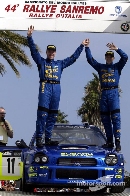 Petter Solberg y su copiloto Phil Mills celebran su tercer lugar en el podio