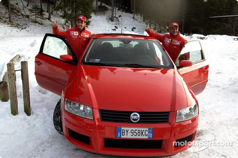 Luciano Burti and Rubens Barrichello arrive in a Fiat Stilo