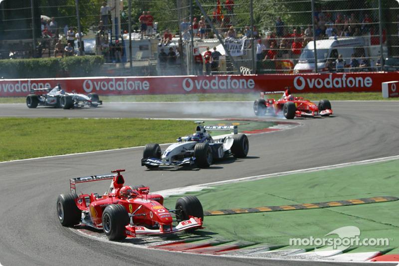 Primera vuelta: Michael Schumacher conduce Montoya mientras que Rubens Barrichello bloquea las llantas