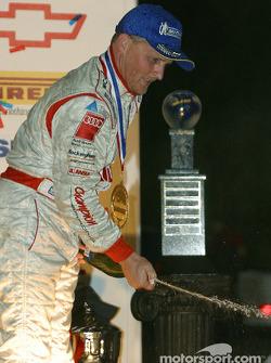 P1 podium: Johnny Herbert sprays champagne on his crew