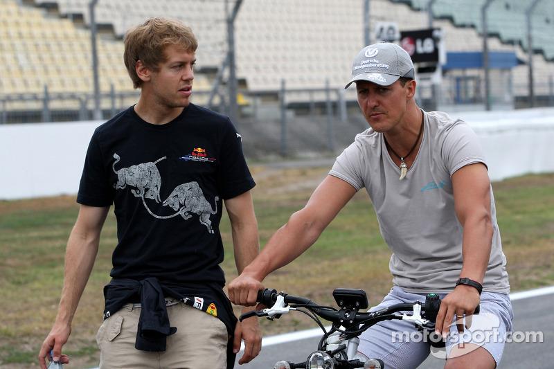 Sebastian Vettel, Red Bull Racing wandelt op het circuit en praat met Michael Schumacher, Mercedes