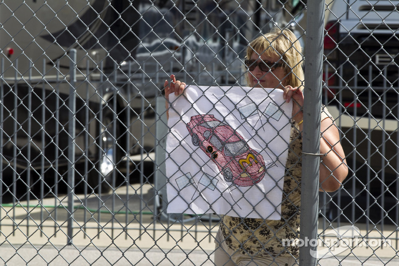 A fan waits outside the garage area to watch the cars