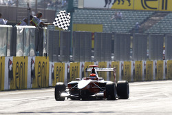 Alexander Rossi celebrates victory as he takes the chequred flag