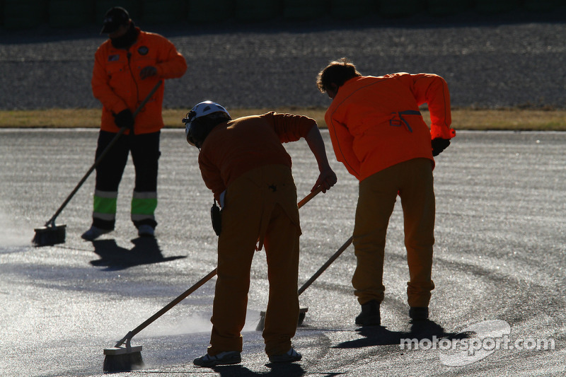 People cleaning the track after Felipe Massa, Scuderia Ferrari blows up his engine