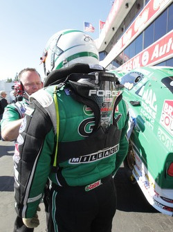 John Force having his restraint system put on by crewmember