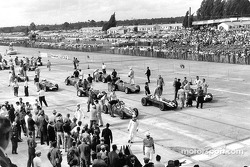 Jack Brabham (car no.8) climbs into his Cooper-Climax on the front row of the grid