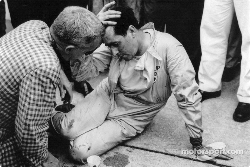 Jack Brabham takes a well-earned rest after pushing his Cooper-Climax half a mile to the finishing line
