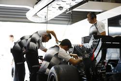 Члены команды McLaren  работают в гараже