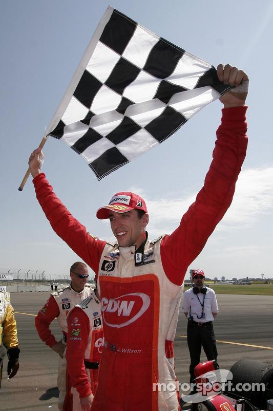 Justin Wilson détient le drapeau à damier pour fêter sa victoire
