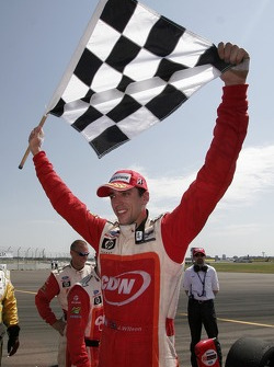 Justin Wilson holds up the checkered flag as he celebrates winning the race