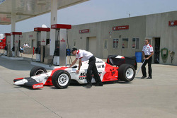 Helio Castroneves' crew brings the car back from the fuel depot