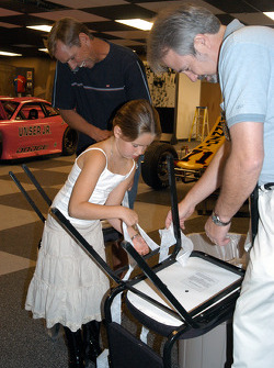 Loni Unser helps father Johnny and Chuck Homier with unwrapping of chairs