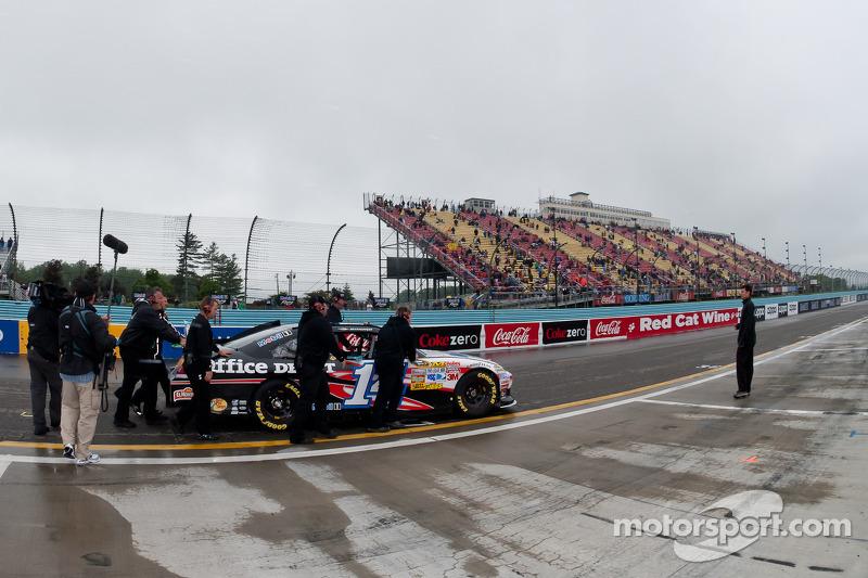Stewart-Haas crewmen push Tony Stewart's car to the pit lane
