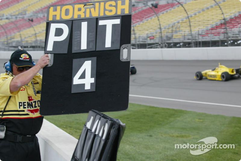 Un membre du Panther Racing indique à Sam Hornish Jr de rentrer au stand