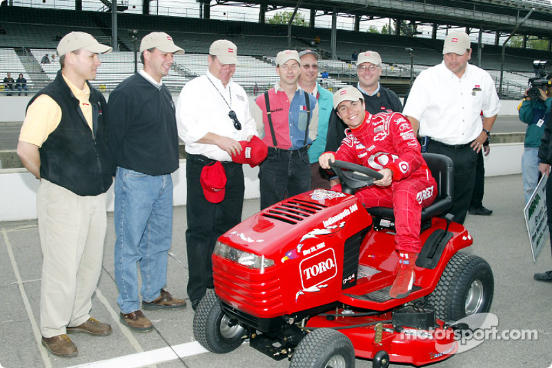 Bruno Junqueira receiving the pole winner trophy: a Toro riding lawnmower