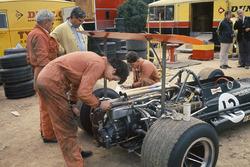 Mecánicos de BRM trabajan en el P133 de Jackie Oliver en el paddock, mientras Tony Rudd mira