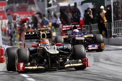 Romain Grosjean, Lotus F1 and Daniel Ricciardo, Scuderia Toro Rosso leave the pits