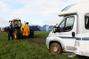 Wet and muddy car parks and camp sites at the circuit as a tractor helps a stuck camper van