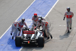 Jenson Button, McLaren MP4-28 is recovered after a bad pit stop